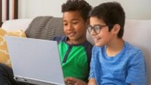 Two boys playing on a computer together